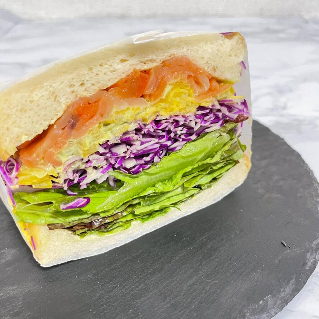 色とりどりの野菜とスモークサーモンを挟んだカラフル野菜とスモークサーモンのサンドウィッチ